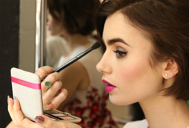 Lily Collins applying makeup